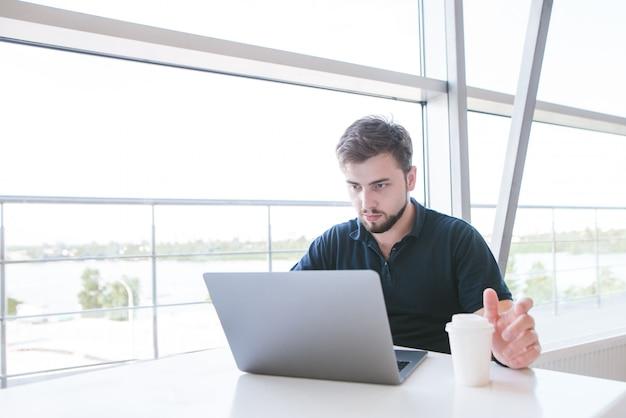 Концентрированный предприниматель сидит в светлом кафе с чашкой кофе в руках и работает на ноутбуке.