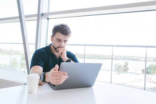 Привлекательный серьезный человек с бородой работает на ноутбуке в кафе возле окна.