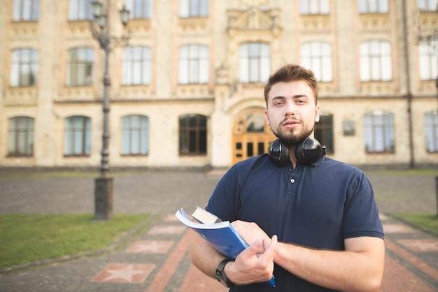 建物の背景の上に立って、カメラを見ている両手で本を持つ男の肖像画。
