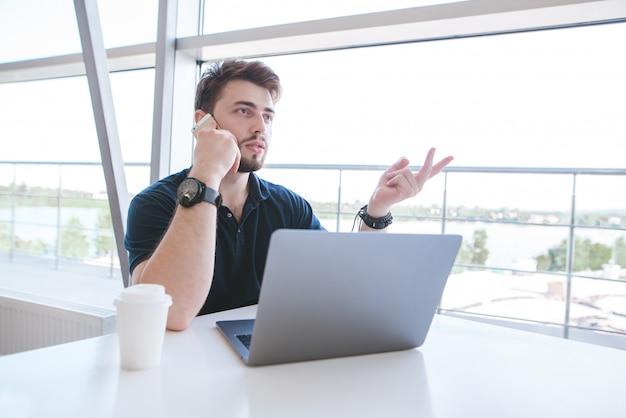 Занятый бизнесмен сидит за столом у окна с бокалом кофе и ноутбуком и разговаривает по телефону.