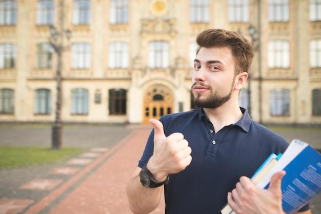 大学の建物の背景の手に本を持ち、親指を現してハンサムな学生の肖像画。