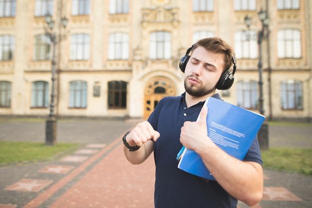 本を手に持って大学の建物の背景に立って、ヘッドフォンで音楽を聴く男性の肖像画。