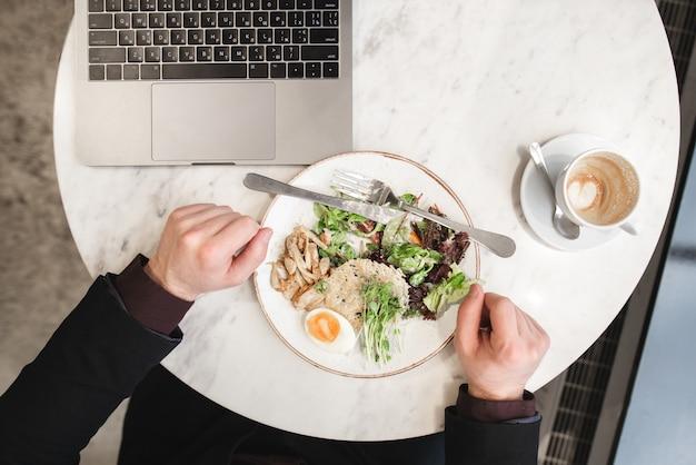 Мужские руки, вилка, нож, тарелка салата, чашка кофе, ноутбук на столе в ресторане.