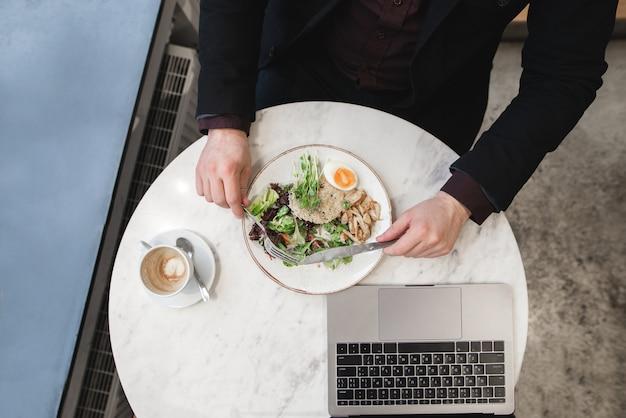 Человек в деловом костюме ест салат, чашку кофе и ноутбук на столе. вид сверху.