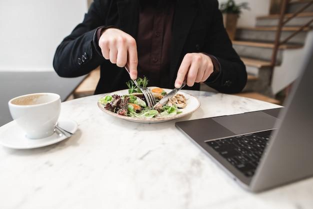 Мужчина в костюме ест салат с вилкой и ножом, чашку кофе и ноутбук стоит на столе в ресторане.