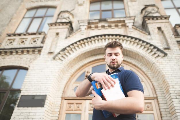 古い大学の建物を背景に本を手にした学生の肖像画。