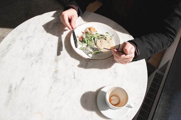 Мужчина ест свежий салат и пьет кофе в светлом ресторане. свет и тень на столе во время еды в ресторане.