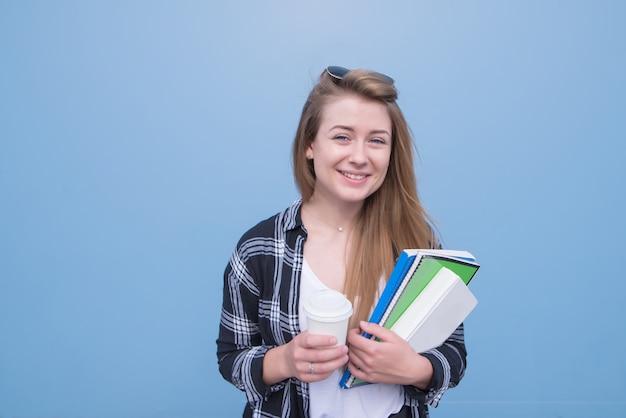 Красивая девушка стоит на синем фоне с чашкой кофе и тетрадями в руках и смотрит в камеру