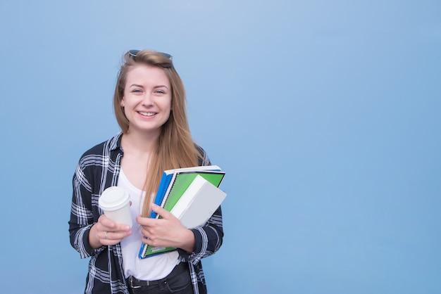 Счастливая девушка с книгами, книгами и чашкой кофе в руках изолирована на синем фоне.