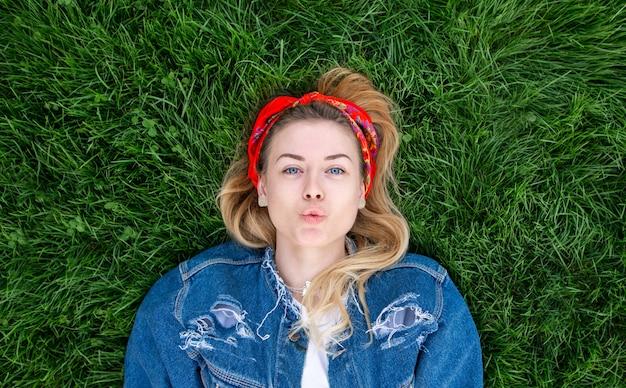 Портрет привлекательная стильная девушка в джинсовой куртке лежал на зеленой лужайке и позирует на камеру