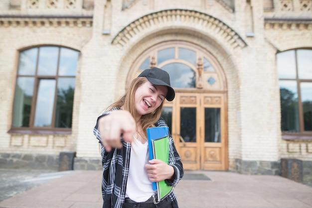 本とノートを大学の建物の背景の手に持って幸せな学生の肖像画。