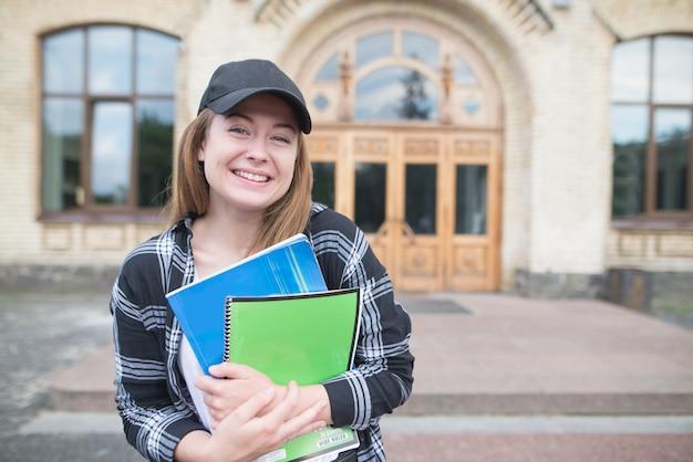 大学の建物を背景に本とノートを手に持つカジュアルな服装の学生。