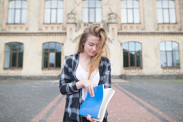 大学の建物を背景に本とノートを手に持ったスタイリッシュなカジュアルドレスの学生。