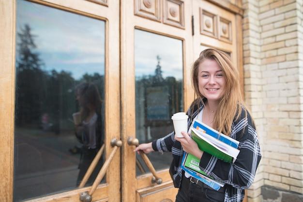 Улыбающаяся студентка, что с книгами. ноутбуки и чашка кофе находятся внутри двери.