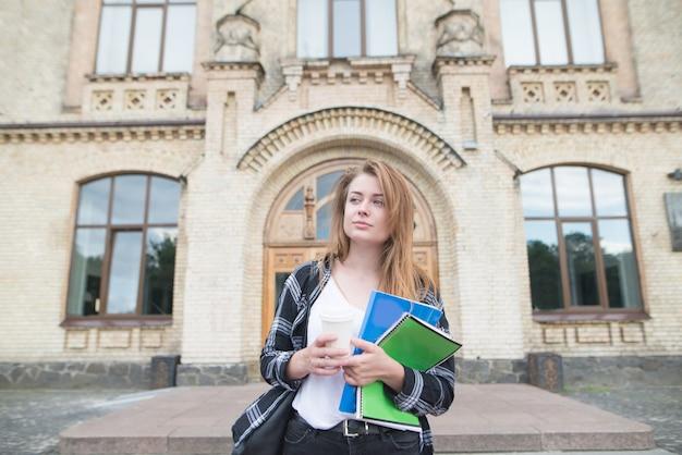 コーヒーと本を手に持つ大学の建物に立っている魅力的な女性の肖像画。