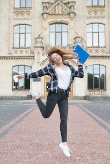 大学の建物の手に本と一杯のコーヒーでジャンプする学生の女の子。