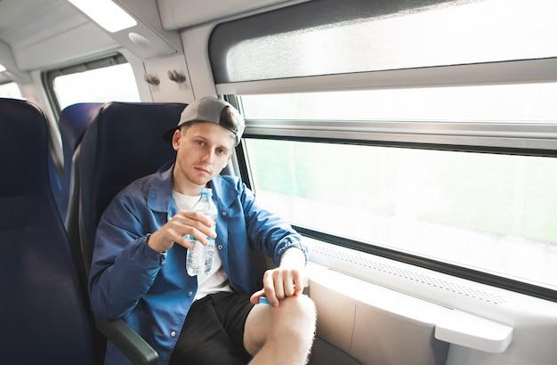 彼の手に水のボトルを持つ窓の近くの電車に座っているハンサムな若い男の肖像