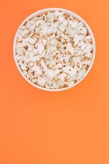Попкорн в бумажный стаканчик на оранжевом фоне сверху. квартира лежала. фильм в кино