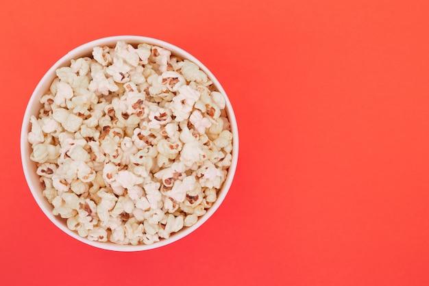 Попкорн в бумажный стаканчик изолирован на красном фоне, вид сверху. плоская планировка