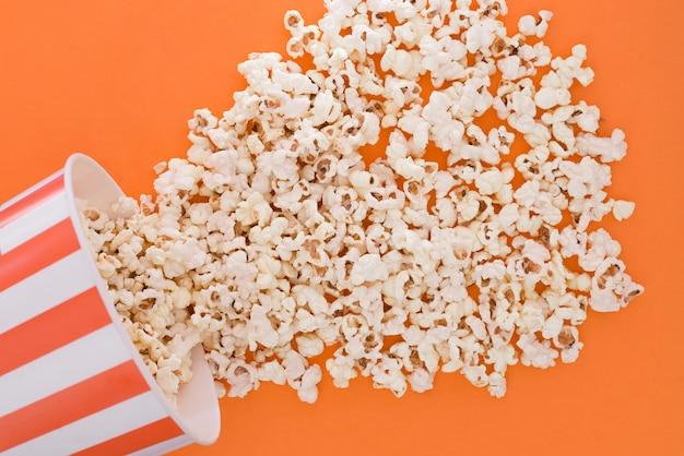 Попкорн бумажный стаканчик на оранжевом фоне, вид сверху. чашка с попкорном изолирован на оранжевом фоне.