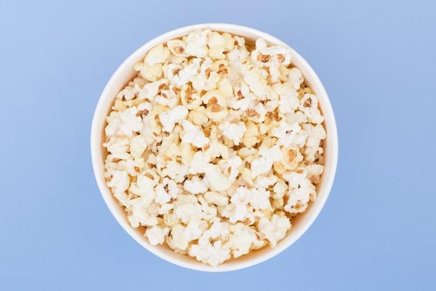 Попкорн в бумажном стаканчике изолирован на пастельной голубой предпосылке, взгляд сверху. плоская планировка