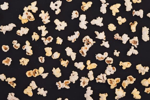 Фон. попкорн на пастельной черной предпосылке, взгляд сверху. концепция кино. квартира лежала.
