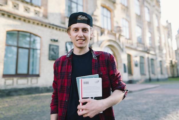 本とノートブックを大学のキャンパスの手に持つシャツを着た若い笑顔の学生。幸せな学生生活。授業後の生活。校庭