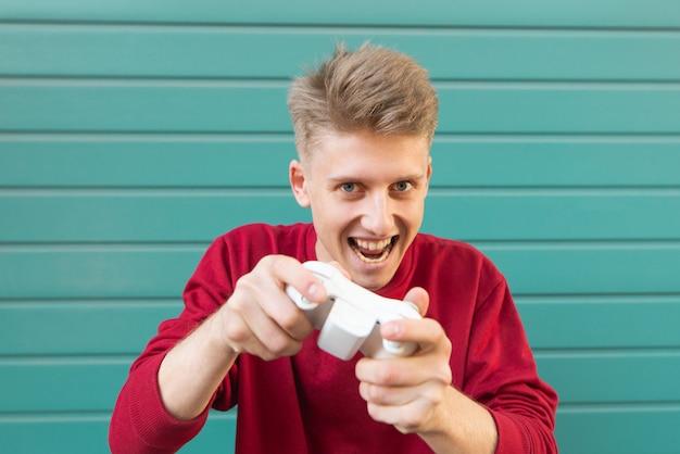 Сумасшедший юный геймер в красной кофте с джойстиком в руке играет в консольные игры.