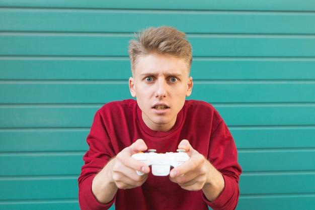 Человек с джойстиком в руках играет в видеоигры на бирюзе