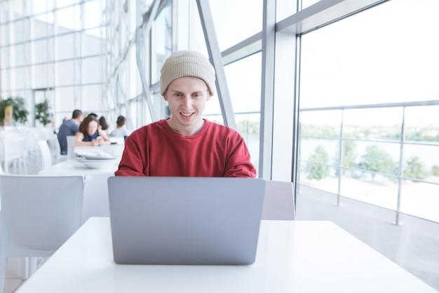 Улыбающийся молодой фрилансер работает с ноутбуком