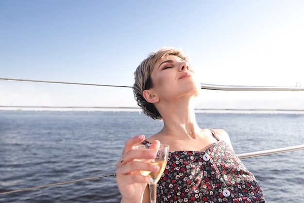 Женщина плывет на яхте и пьет вино