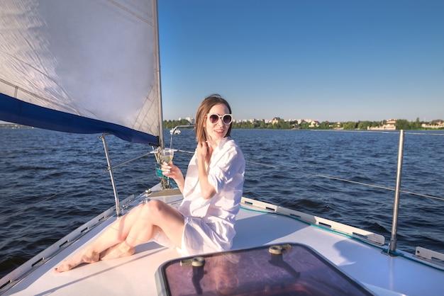 Привлекательная женщина отдыхает на корабле с бокалом вина