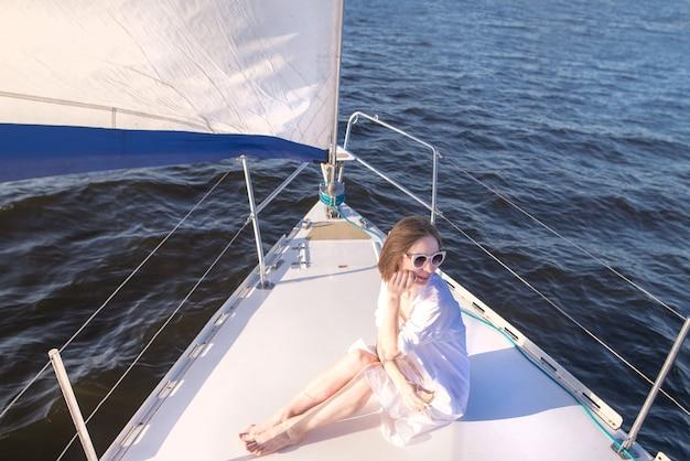 Женщина в очках плавает вечером на яхте у моря с бокалом вина