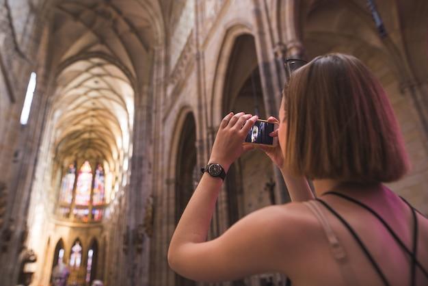 観光客の女の子が古い歴史的な教会のスマートフォンでインテリアの写真を作る