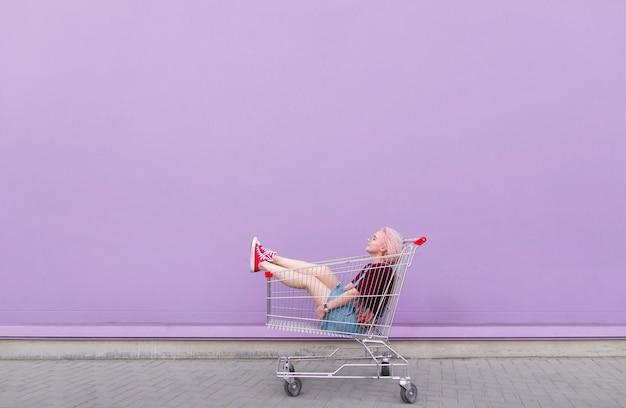 紫色の壁の背景にカートを持つ若いモデルのポーズ
