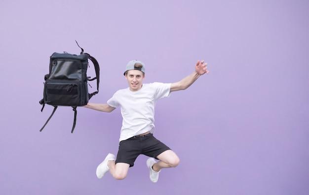 Молодой человек в белой футболке прыгает с рюкзаком на фоне фиолетовой стены