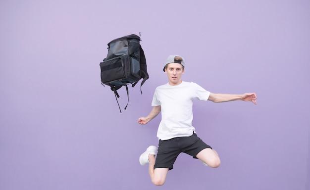 Человек в белой футболке прыгает с рюкзаком на фиолетовом фоне