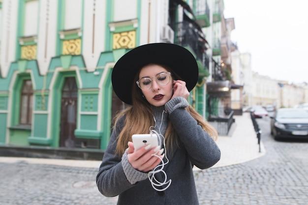 Портрет стильной женщины слушая к музыке в наушниках на фоне красивого старого города.