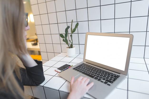 Студент учится в кафе за ноутбуком. рабочее пространство фрилансера в кафе.