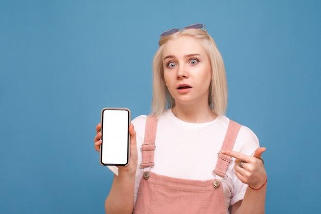 驚いた女の子は軽いカジュアルな服を着て、白い画面でスマートフォンを持ち、画面に指を示しています