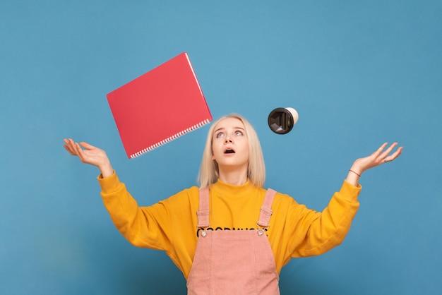 Эмоциональная девушка в ярком повседневном платье стоит на синем и подбрасывает чашку кофе и блокнот.