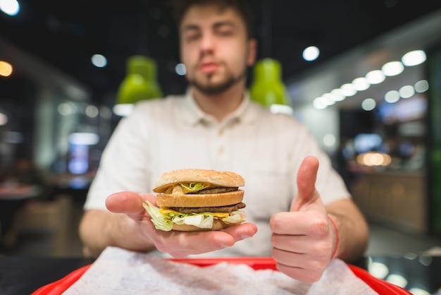 Мужчина держит большой бургер в руке и показывает большой палец вверх. мужчина любит фаст-фуд. вкусный гамбургер в ваших руках.