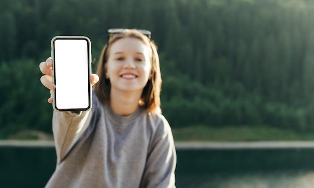 Портрет вид спереди улыбается женщина путешественник, показывая смартфон пустой экран на горном лесу