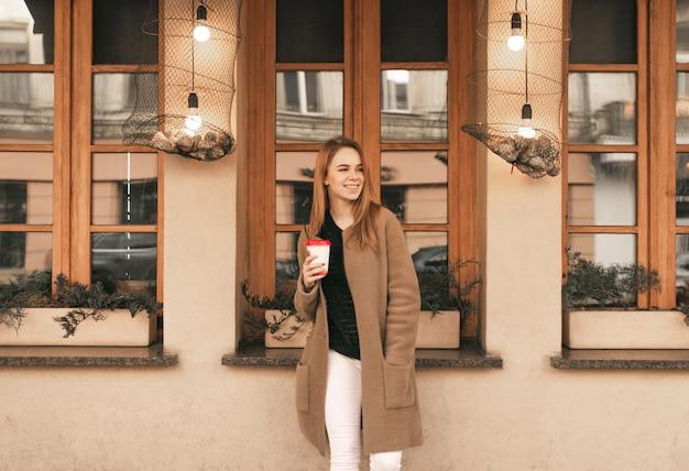 Счастливая девушка в пальто и чашке кофе в руках, одетая в пальто, стоит на фоне коричневой стены и окна ресторана
