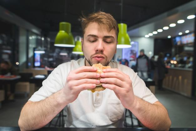 Голодный человек смотрит на бутерброд в руках. мужчина собирается съесть отличный аппетитный бургер