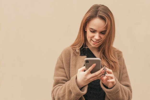 Привлекательная девушка в бежевом пальто стоит с смартфоном в руках бежевой стены, смотрит на экран смартфона и улыбается