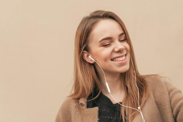 クローズアップの肖像画が彼女のヘッドフォンで彼女の目を閉じて、笑顔で音楽を聴く、ベージュの壁の背景
