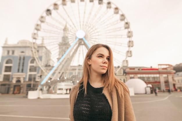 Привлекательная женщина в пальто позирует на фоне колеса обозрения и улицы