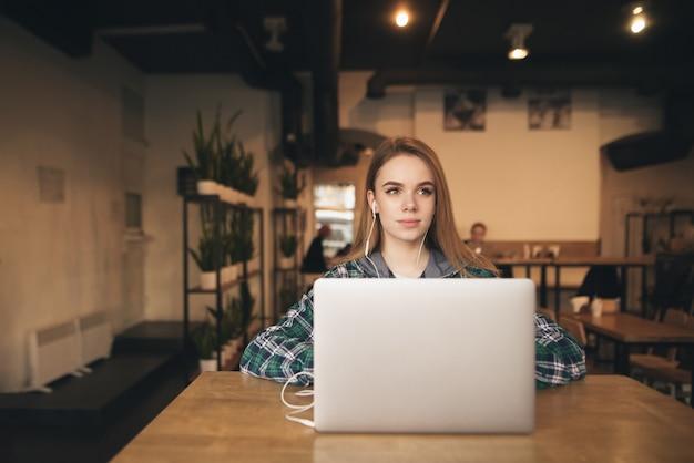 ヘッドフォンとカジュアルな服を着て魅力的な女の子はカフェでラップトップに取り組んでいます