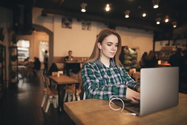 かわいい女の子は居心地の良いカフェのラップトップで作業し、ヘッドフォンで音楽を聴いたり、カジュアルな服を着たり、画面を見ることに集中しています。